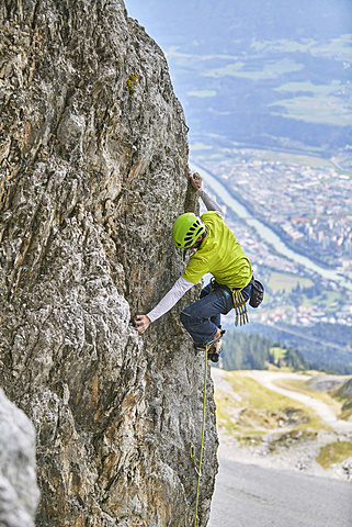 Climber with helmet climbing on a rock wall, behind Innsbruck, Northern Alps, Tyrol, Austria, Europe