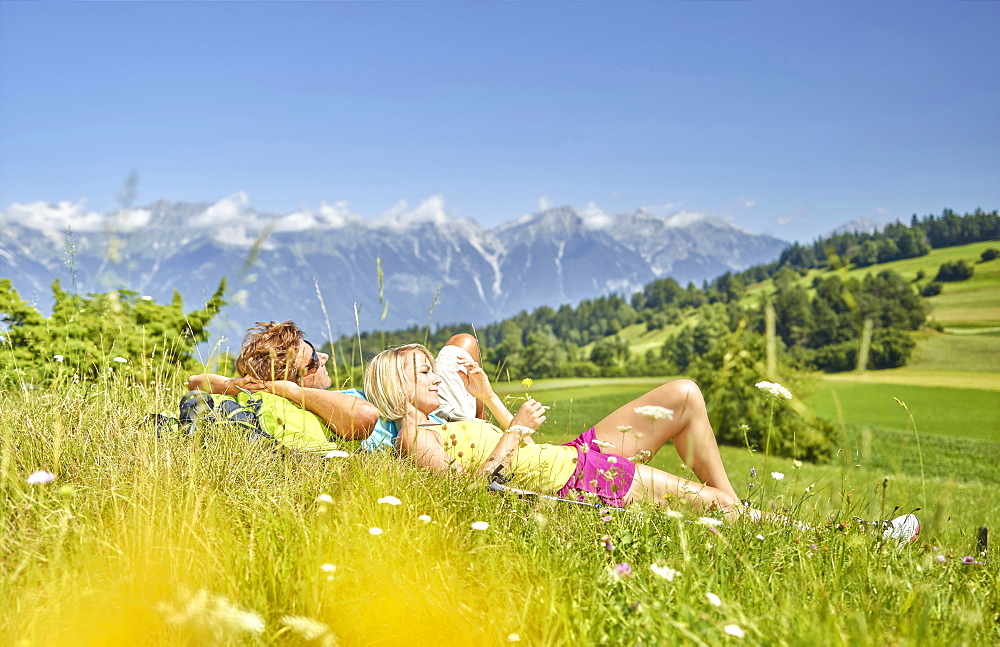 Man and woman lying in a flower meadow with a view of the North Chain, Patsch, Innsbruck, Austria, Europe - 832-378677