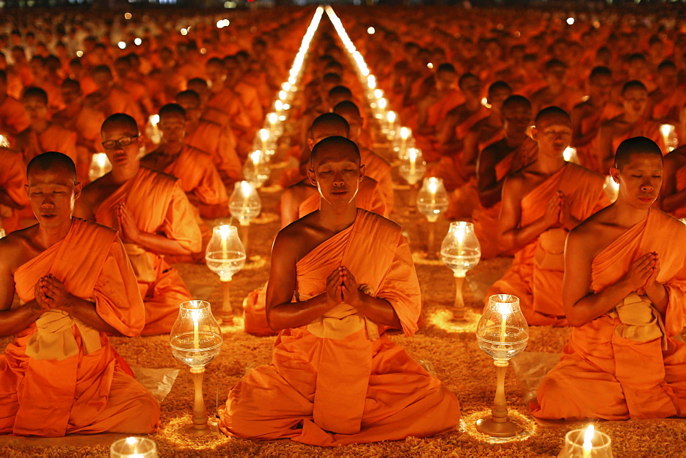 Monks sitting in rows praying and meditating by candlelight, Wat Phra Dhammakaya Temple, Khlong Luang District, Pathum Thani, Bangkok, Thailand, Asia