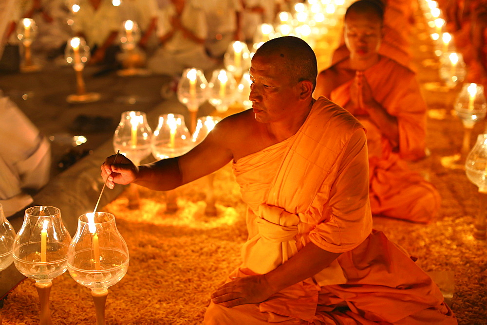 Monk lights candle, meditation, Wat Phra Dhammakaya Temple, Khlong Luang District, Pathum Thani, Bangkok, Thailand, Asia