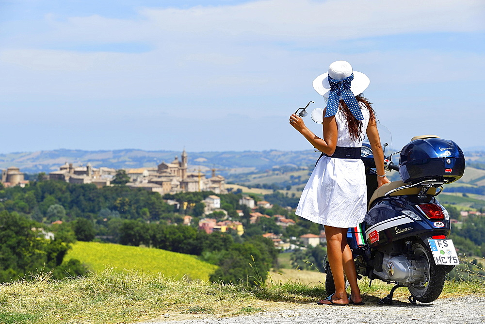 Woman with white sunhat next to Vespa Primavera scooter, Corinaldo, Marche, Italy, Europe