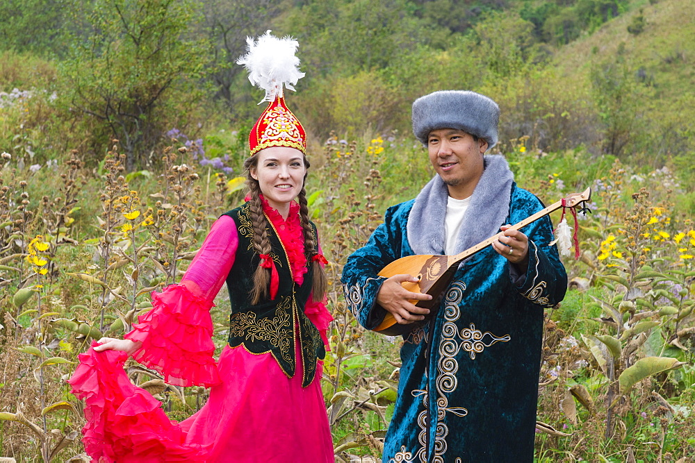 Kazakh man singing and playing the dombra for a woman, Kazakh ethnographic village aul Gunny, Talgar, Almaty, Kazakhstan, Asia
