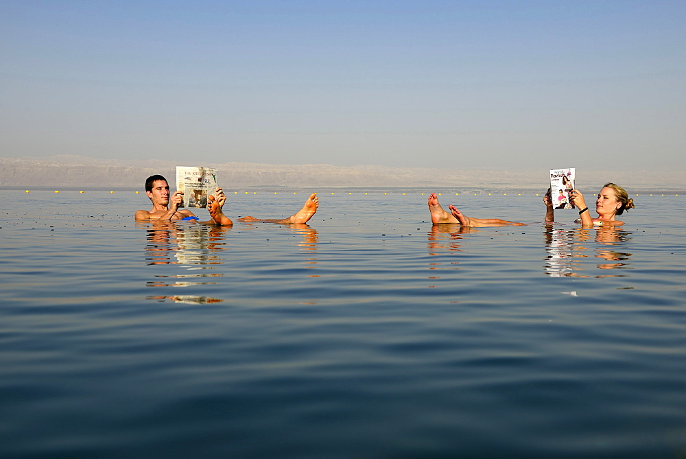 Young couple reads newspaper floating in Dead Sea, Jordan, Asia