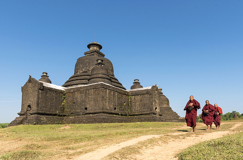 Buddhist monks collect morning alms in front of Laymyetnha Paya, Lemyethna Temple, Mrauk U, Burma, Myanmar, Asia
