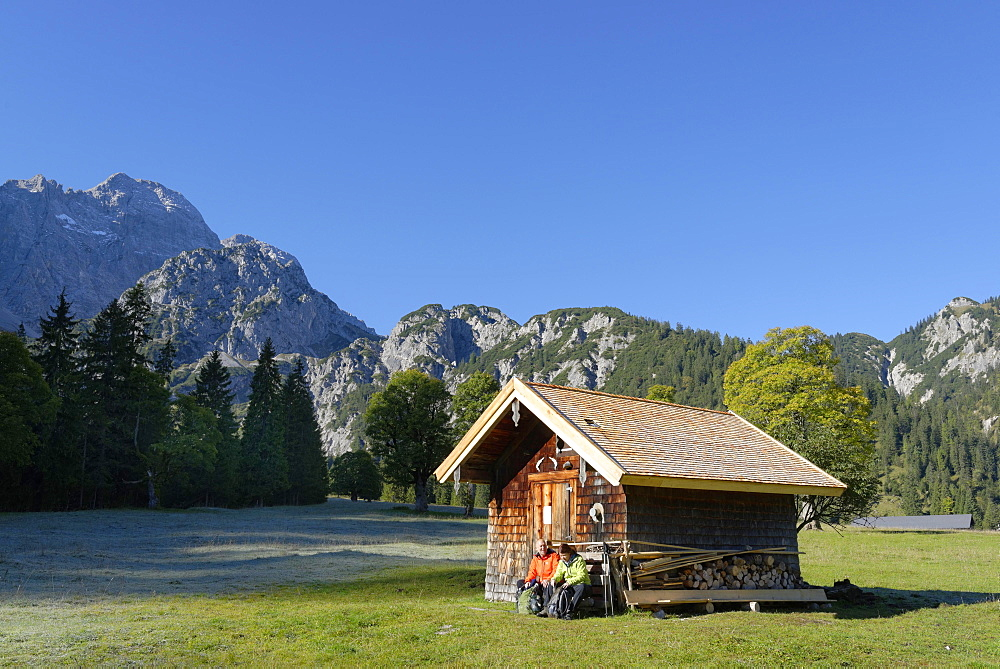 Hikers resting wooden hut, snacking, Rohntal at Purschalm, Eng, Karwendel, Risstal, Rissbachtal, Tyrol, Austria, Europe