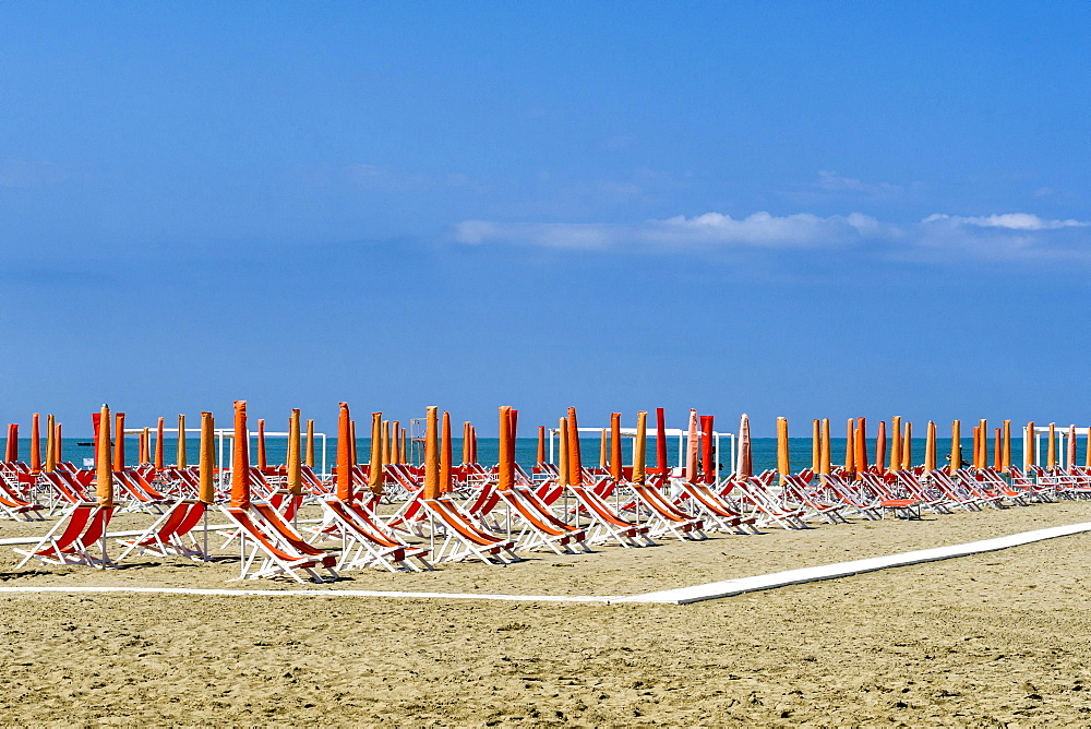 Empty orange deckchairs and sunshades on beach, early season, Viareggio, Tuscany, Italy, Europe