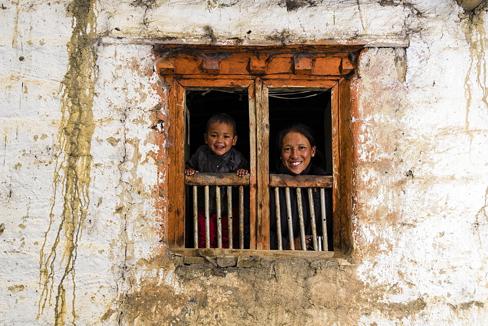 Young woman and son looking out of farmhouse window, Purang, Mustang District, Nepal, Asia
