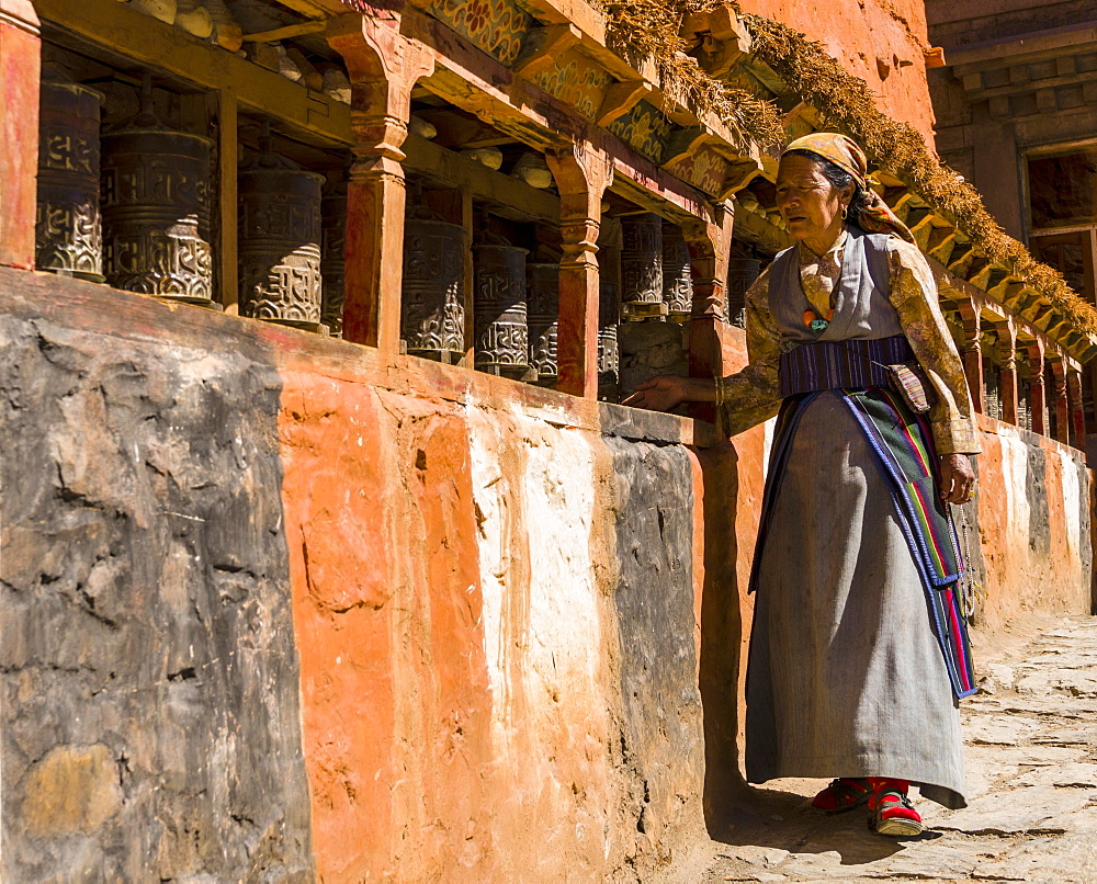 Native woman walking along Mani Wall and spinning prayer wheels, Kagbeni, Mustang District, Nepal, Asia