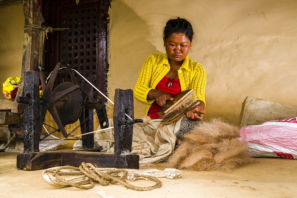Native woman spinning sheep's wool with traditional spinning wheel in front of house, Ghandruk, Kaski District, Nepal, Asia - 832-379969