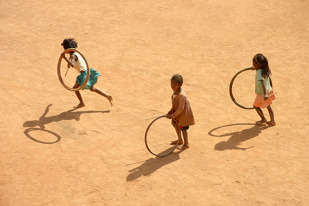 Children playing with tires on village street, Bevato, Tsiroanomandidy district, Bongolava region, Madagascar, Africa - 832-379976