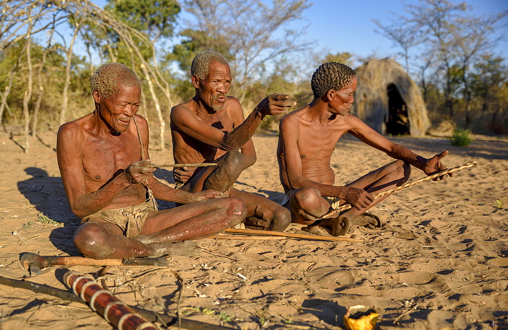 Bushmen of Ju/' Hoansi-San sitting on the ground, village //Xa/oba, near Tsumkwe, Otjozondjupa region, Namibia, Africa