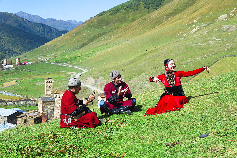 Georgian people of a folkloric group playing Panduri and dancing in traditional Georgian clothes, Ushguli, Svaneti region, Georgia, Asia