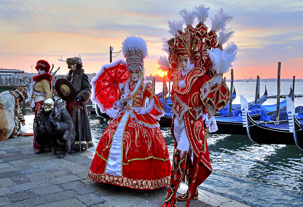 Disguised couple with Venetian masks at the lagoon, behind island San Giorgio, carnival in Venice, Italy, Europe