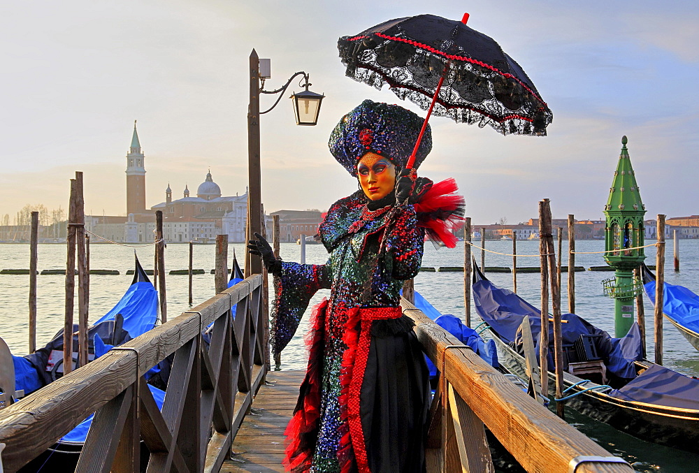 Female disguised with Venetian mask on walkway at the lagoon, behind island of San Giorgio, carnival in Venice, Italy, Europe
