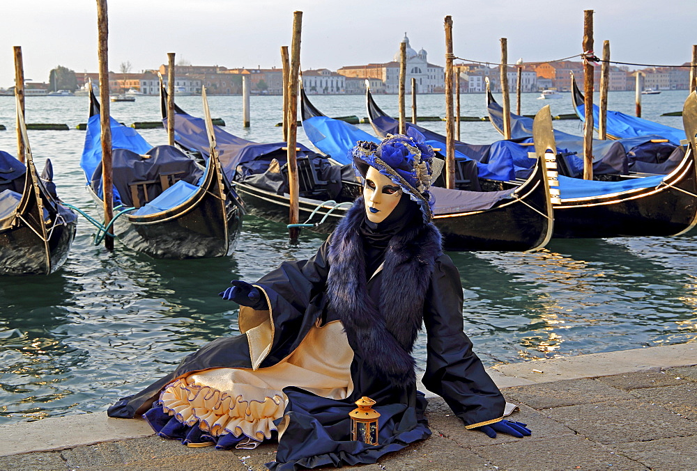 Woman with Venetian mask sitting at the lagoon, behind San Giorgio, carnival in Venice, Venice, Italy, Europe