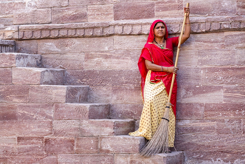 Woman in Sari sweeping steps, resting, Toorji Ka Jhalara, The Step Well, Jodphur, Rajasthan, India, Asia