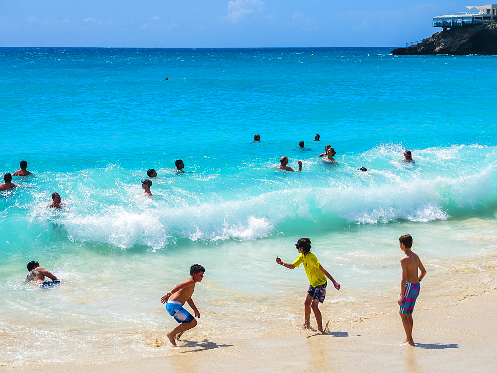 Tourists bathing in high waves at Maho Beach, Simson Bay Village, Philippsburg, Caribbean, Sint Maarten, North America