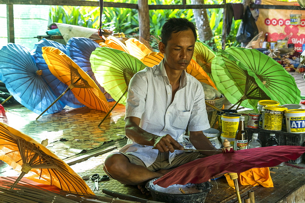 Local man working on multi-colored umbrellas, Pathein, Myanmar, Asia