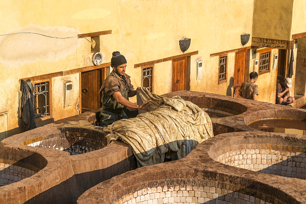 Leather tanners on tanks with paint for dyeing leather, dyeing, tannery Tannerie Chouara, tanner and dyeing district Fes el Bali, Fez, Morocco, Africa