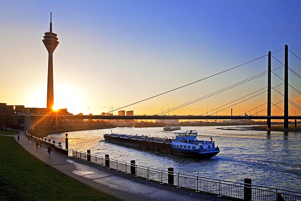 Rhine with cargo ship, Rhine Tower and Rheinkniebrücke, bridge at sunset, Düsseldorf, North Rhine-Westphalia, Germany, Europe