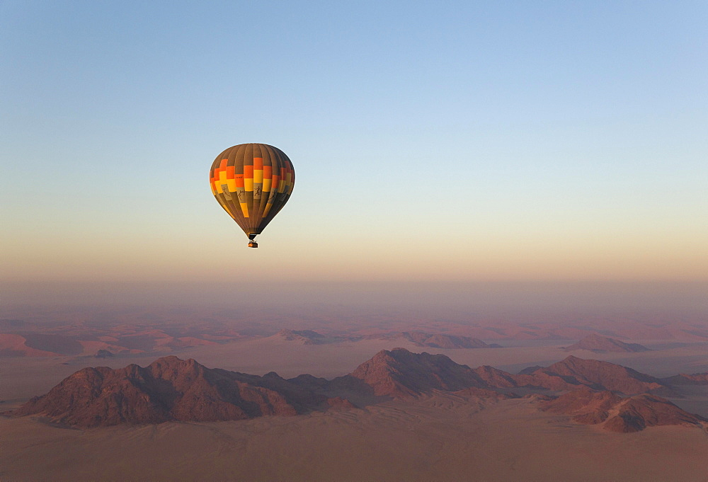 Hot-air balloon above an arid plain and isolated mountain ridges, at dawn, Namib Desert, aerial view from a second balloon, NamibRand Nature Reserve, Namibia, Africa