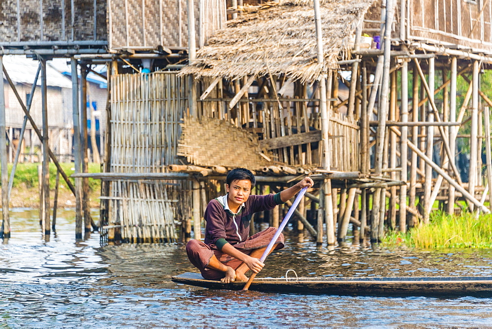 Boy, young man rowing, traditional stilt houses behind, Inle Lake, Nampan, Shan State, Myanmar, Asia