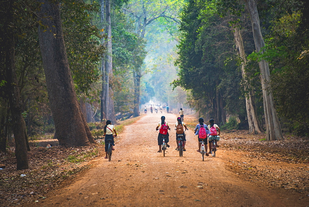 Local children ride bicycles, way to school, Angkor Archaeological Park, Siem Reap Province, Cambodia, Asia