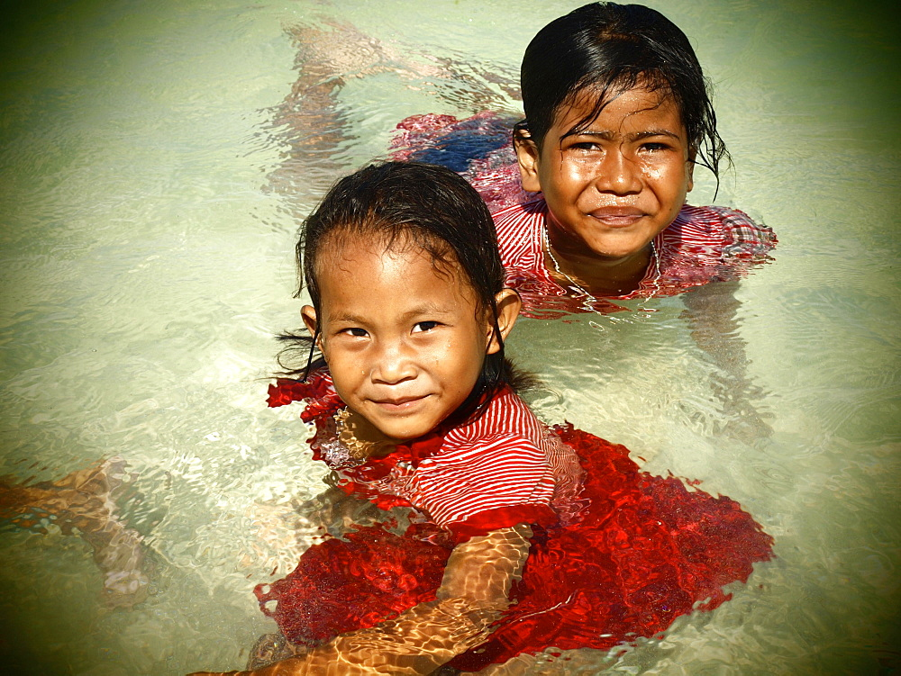 Two girls, 6 years, swimming fully dressed on the beach of Koh Bulong, Thailand, Asia