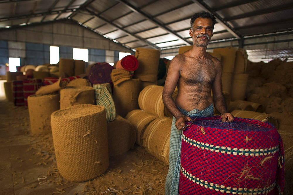 Worker with rolled coconut fibre mats or coir mats, coconut fibre industry, factory, Alappuzha, Kerala, India, Asia