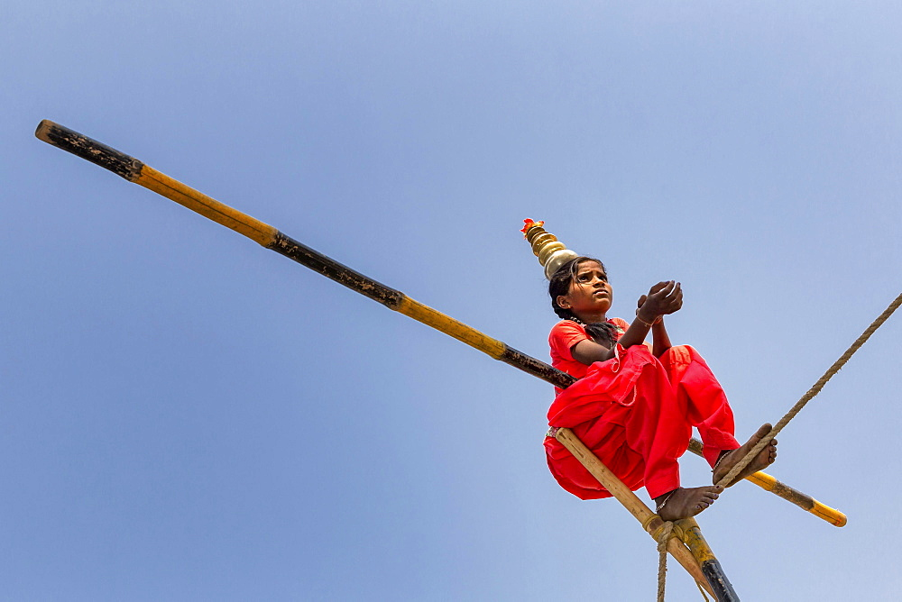 Young girl balancing a on rope, Pushkar, Rajasthan, India, Asia