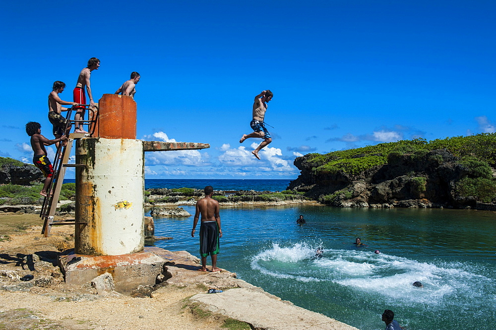 Local boys jumping and swimming in the Salugula Pool, Guam, US Territory, Pacific, Oceania