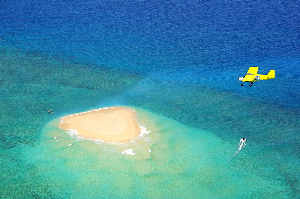 Small plane flying over coral reef with sand island, near Grande Terre island, Mayotte, Africa