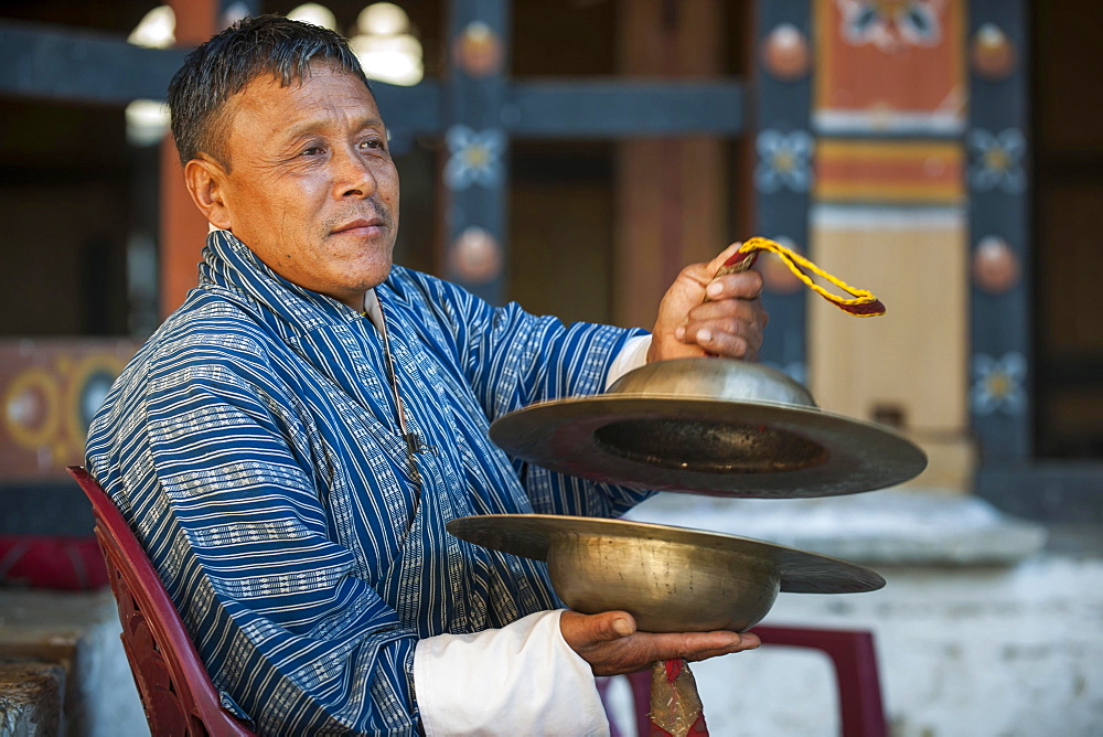 A man with cymbals at a temple festival, Mongar District, Himalayas, Kingdom of Bhutan - 832-381692