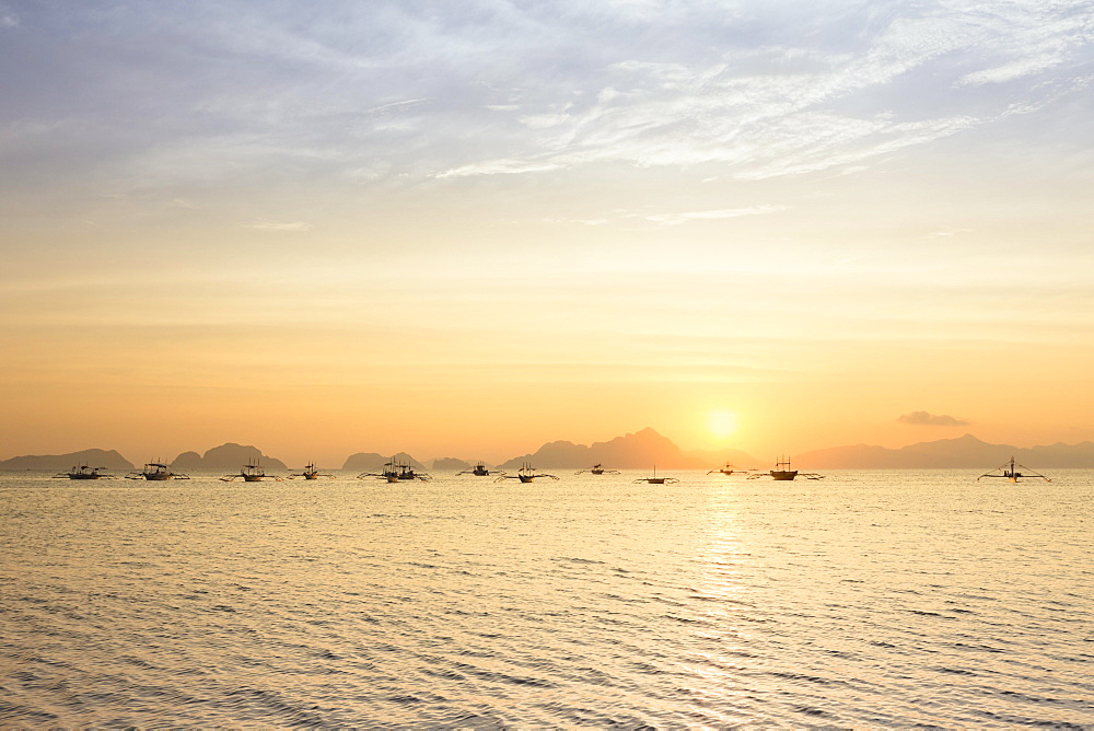Outrigger canoes at sunset, view from Corong Corong beach near El Nido, Bacuit archipelago, Palawan island, Philippines, Asia
