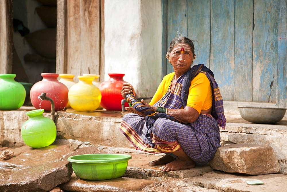 Elderly woman washing her hands, Aihole, Karnataka, India, Asia