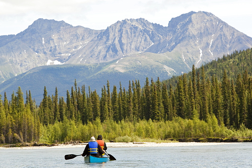 Two men in a canoe, canoeists paddling, canoeing upper Liard River, Pelly Mountains behind, Yukon Territory, Canada, North America