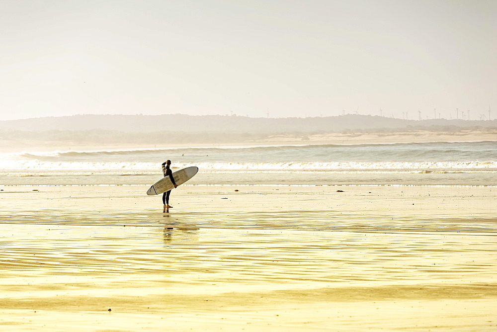 Surfer standing on the beach, watching the surf, Plage Tagharte, Essaouira, Morocco, Africa