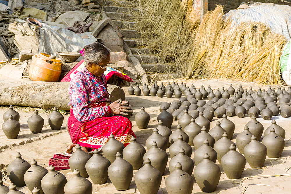 A woman is working at pottery in the streets, Bhaktapur, Kathmandu, Nepal, Asia - 832-382079