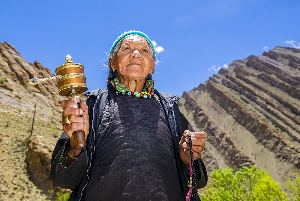 An old Ladakhi woman is turning a prayer wheel, Hemis Gompa, Hemis, Jammu and Kashmir, India, Asia