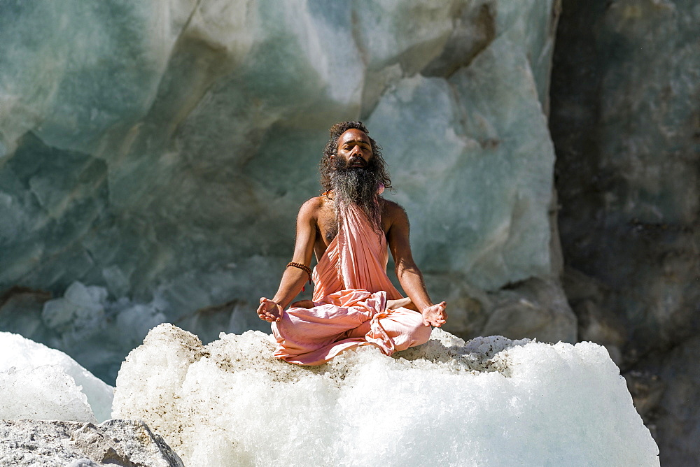 A Sadhu, holy man, is sitting and meditating in lotus pose, padmasana, on a block of ice at Gaumukh, the main source of the holy river Ganges, Gangotri, Uttarakhand, India, Asia