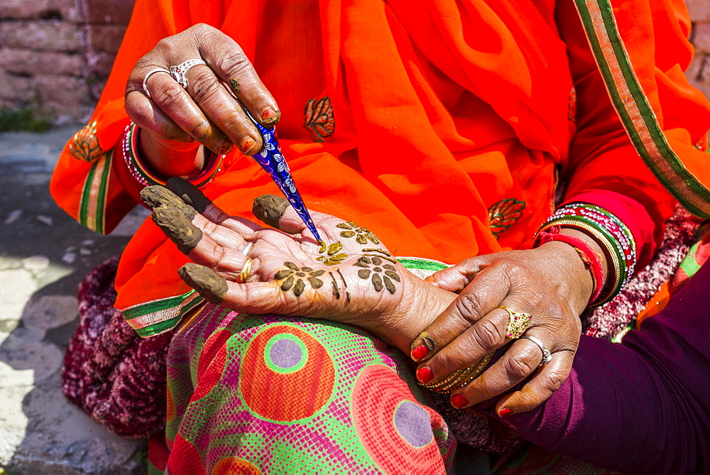 An indian woman is painting a hand with henna, in front of Badrinath Temple, one of the Dschar Dham destinations, Badrinath, Uttarakhand, India, Asia