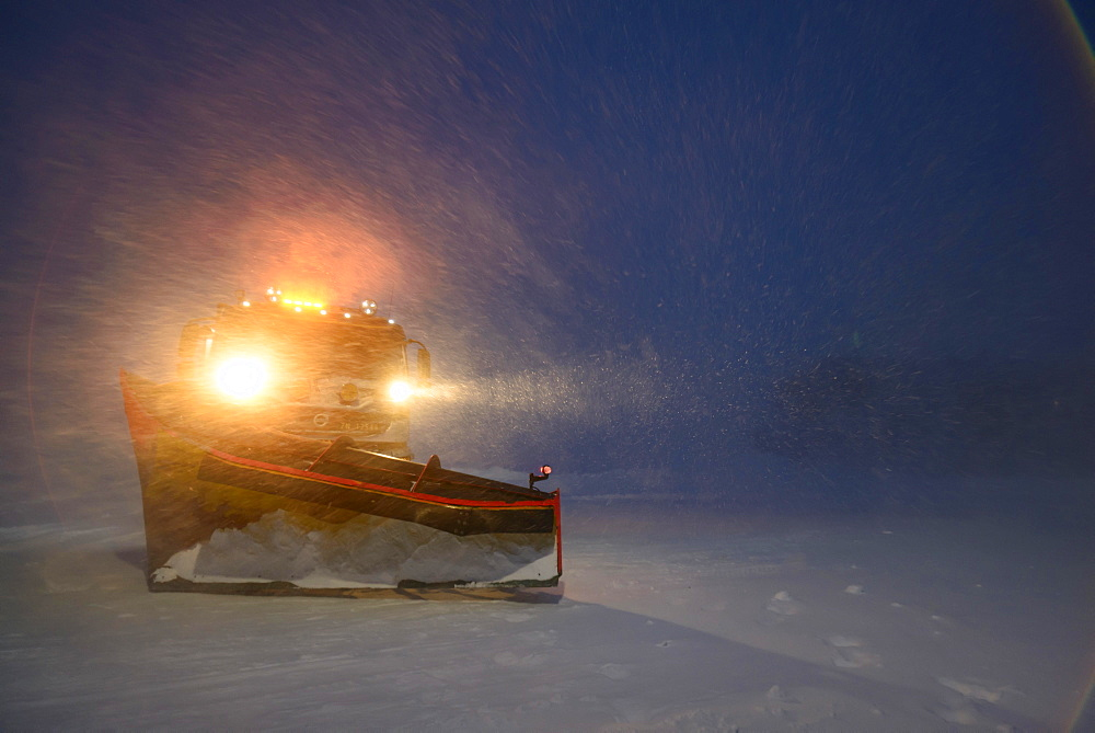 Snowplow in the arctic blizzard during the polar night, Longyearbyen, Svalbard, Norway, Europe