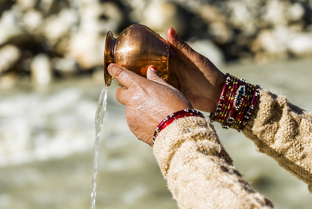A female pilgrim praying, offering the holy water, at the banks of the river Ganges, Gangotri, Uttarakhand, India, Asia