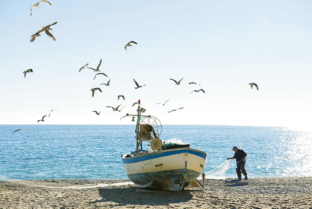 Fisherman with a fishing boat on the beach of Noli, Riviera di Ponente, Liguria, Italy, Europe