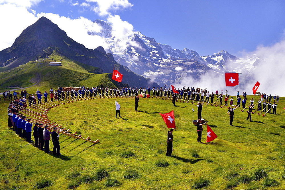 Alphorn blowers and flag throwers, Grosses Alphorntreffen festival, on Mannlichen mountain, Kleine Scheidegg pass, Canton of Bern, Switzerland, Europe