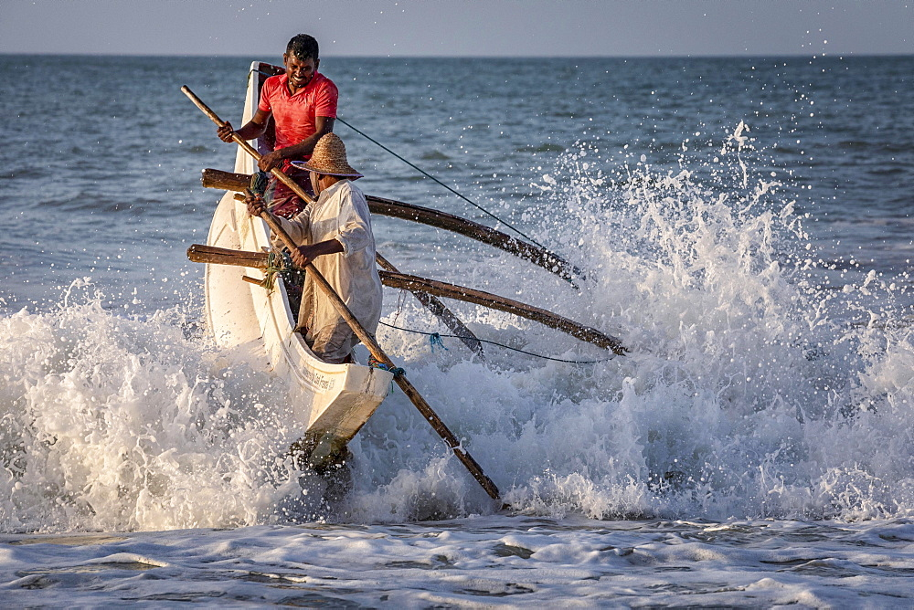 Fishermen breaking the waves at Kahandamodara beach, Sri Lanka, Asia