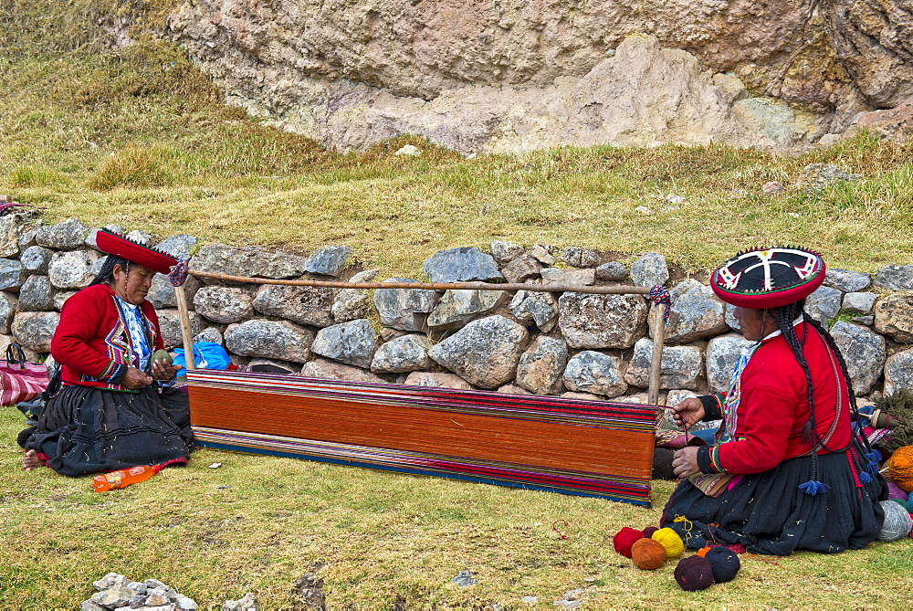 Two elderly women wearing hats, Quechua Indians in traditional dress, squatting on the floor working on the stretcher of a loom, Cinchero, Urubamba Valley, Peru, South America