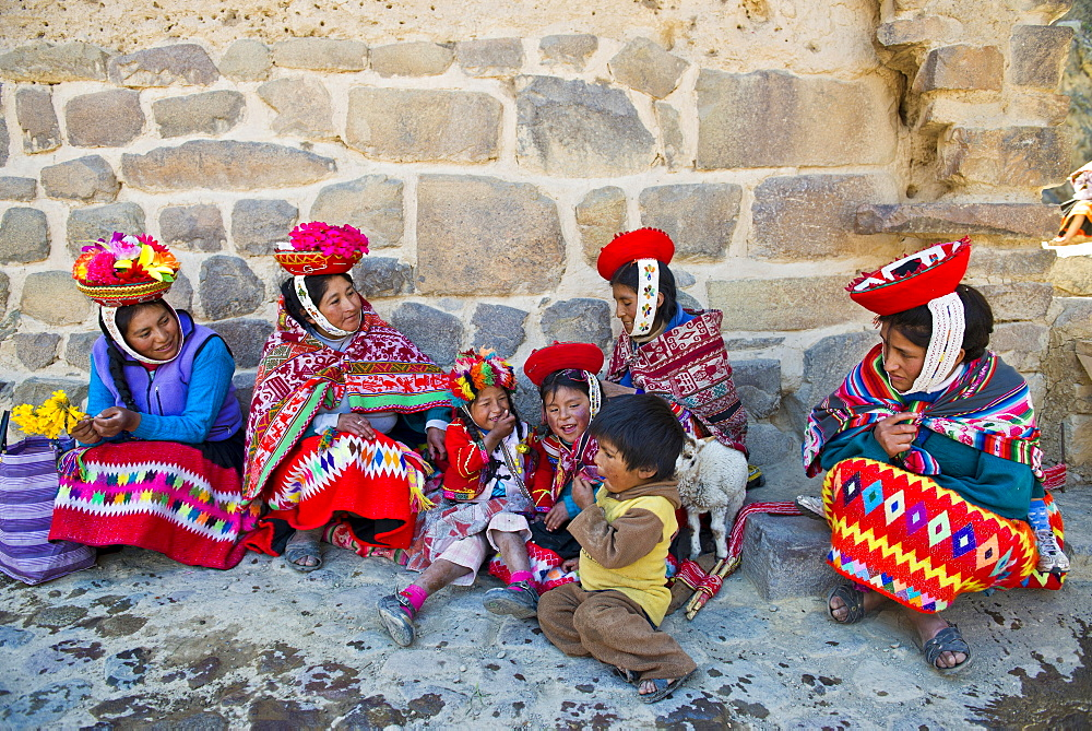 Women and children in traditional dress of the Quechua Indians sitting on the floor in front of a wall, Ollantaytambo, Urubamba Valley, Peru, South America