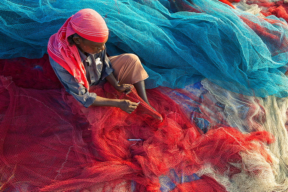 Fisherman repairing fishing nets, Varkala, Kerala, India, Asia