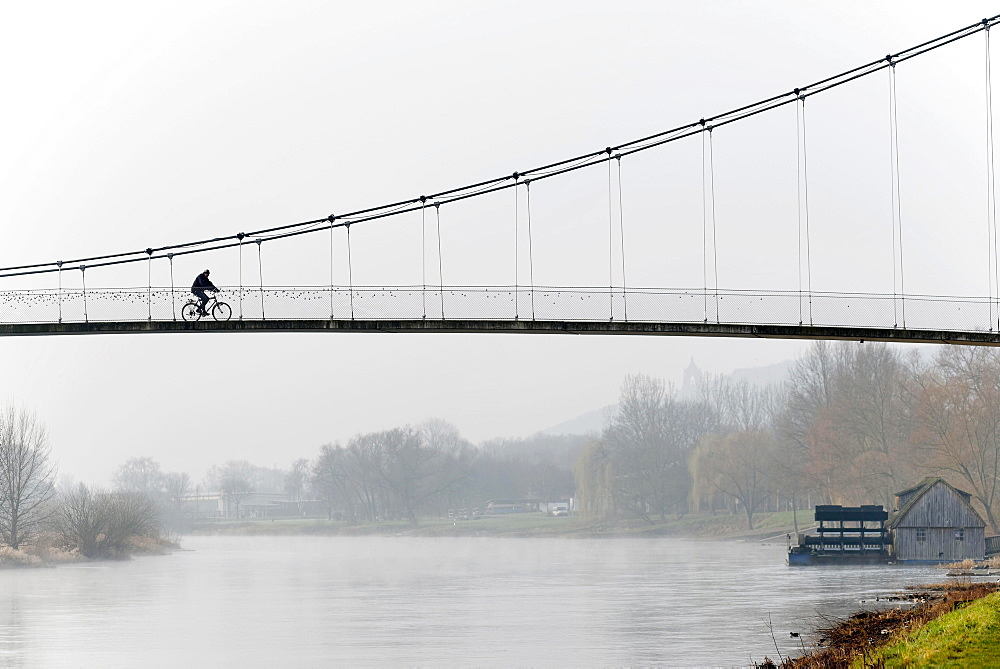 Cyclist crossing a suspension bridge, water mill on the Weser river, Minden, North Rhine-Westphalia, Germany, Europe